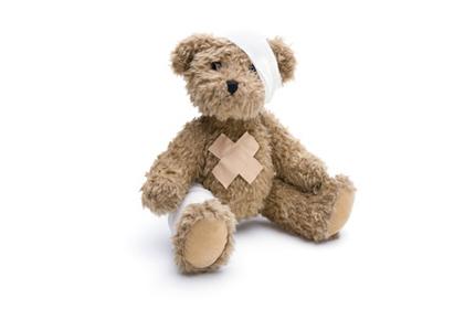Teddy mit Pflaster & Kopfverband: bildlich für Geburtsschäden im Arzthaftungsrecht.