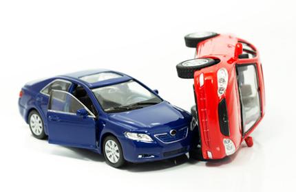 Zwei Spielzeugauto in Unfallsituation: symbolisch für Unfall, Personenschaden, Schmerzensgeld &Schadensersatz.